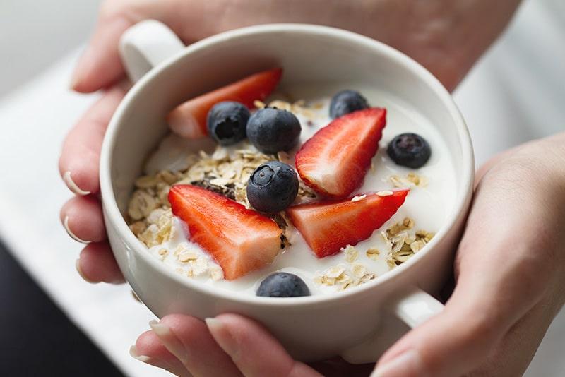 Desayuno yogurt, avena, ciruelas y fresas